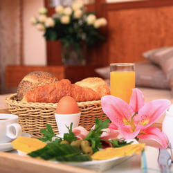 basket of bread with an egg and orange juice
