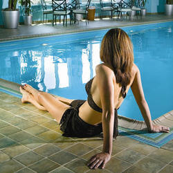 woman laying by indoor pool