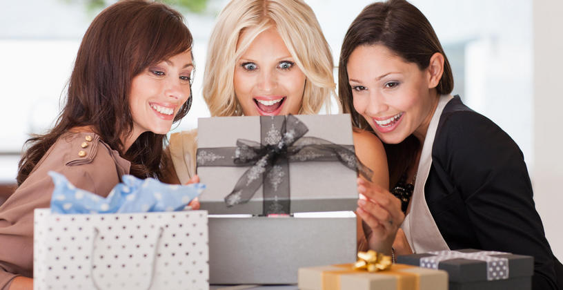 three woman looking into a gift box