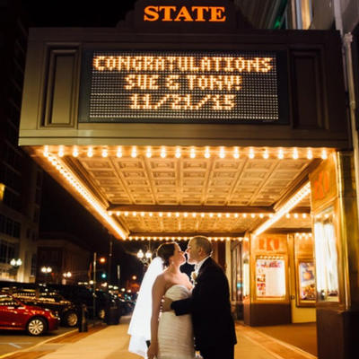 bride and groom standing in front of a theater sign