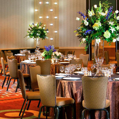 wedding reception setup with circular tables and large flower centerpieces
