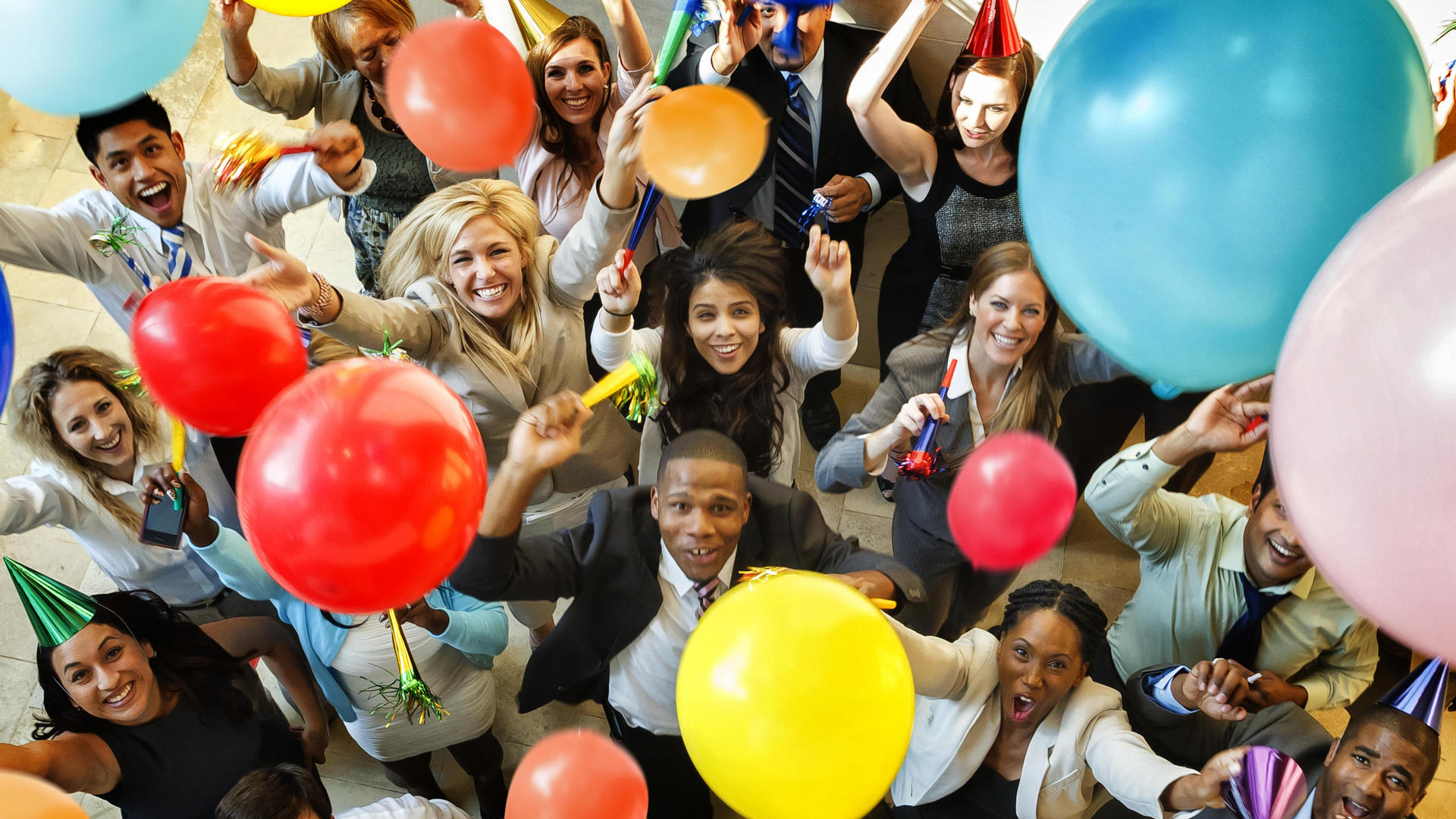 large group of people looking up and celebrating with balloons