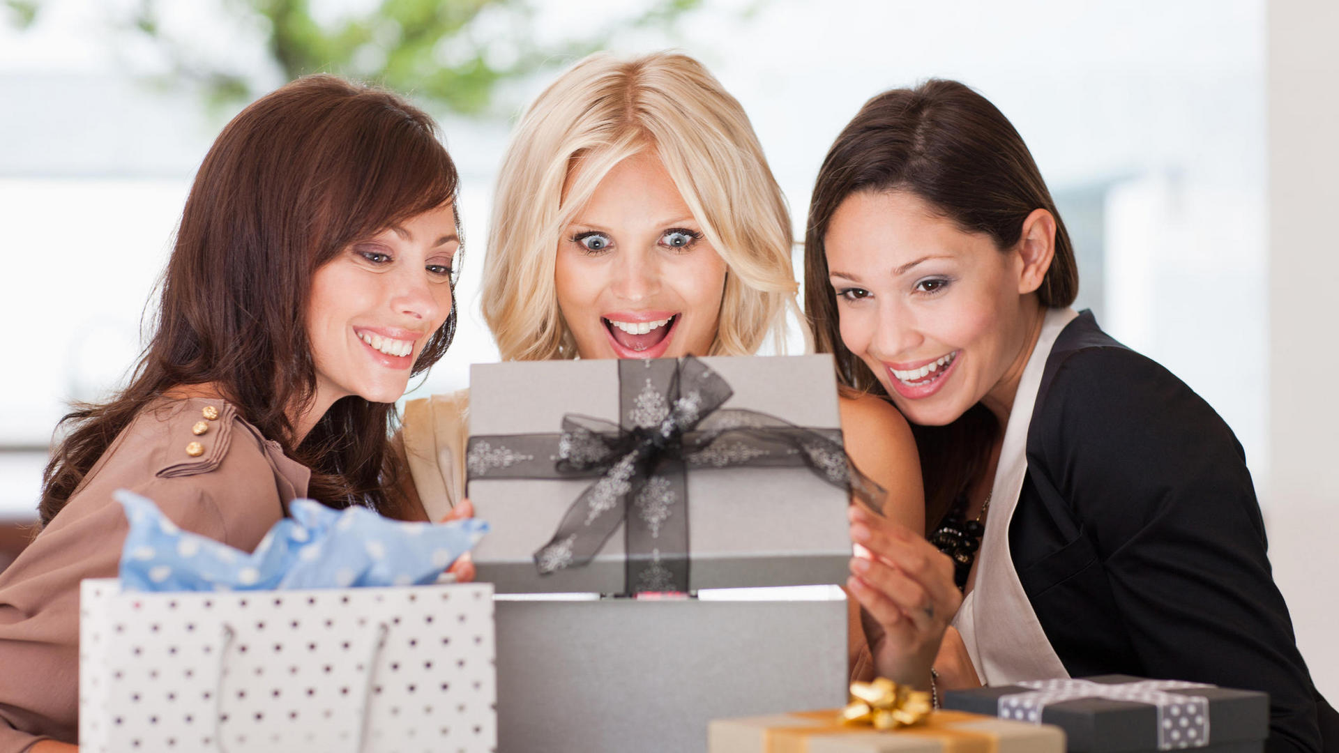 three women looking into a gift box