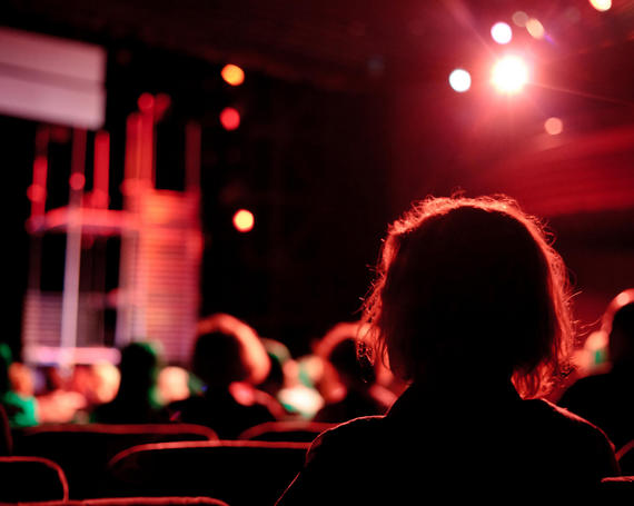 back of person's head sitting in theater