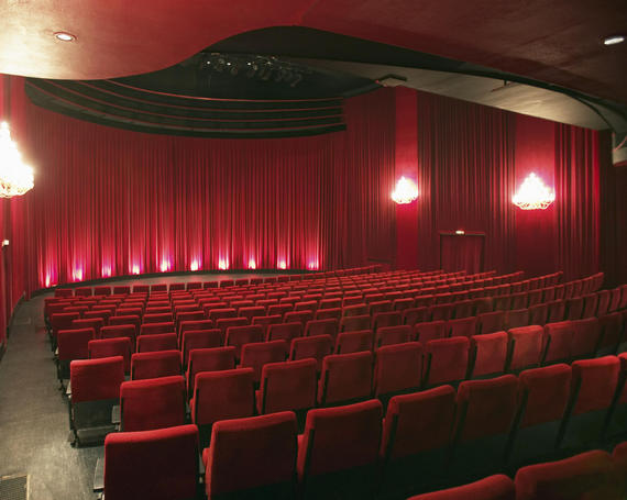 theater with red seats and red curtains