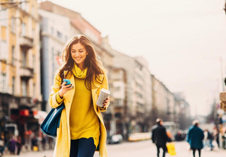 woman walking on the sidewalk holding coffee and a phone