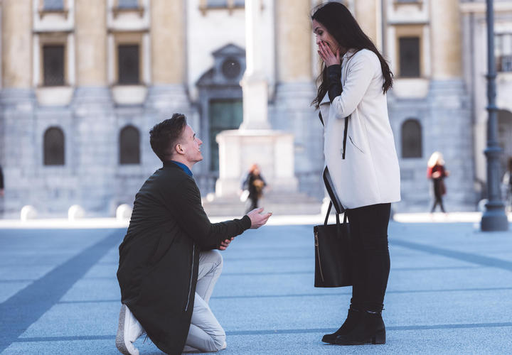 man proposing to girlfriend in city square