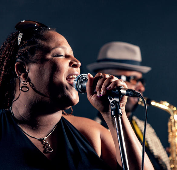Woman singing and man playing the saxophone