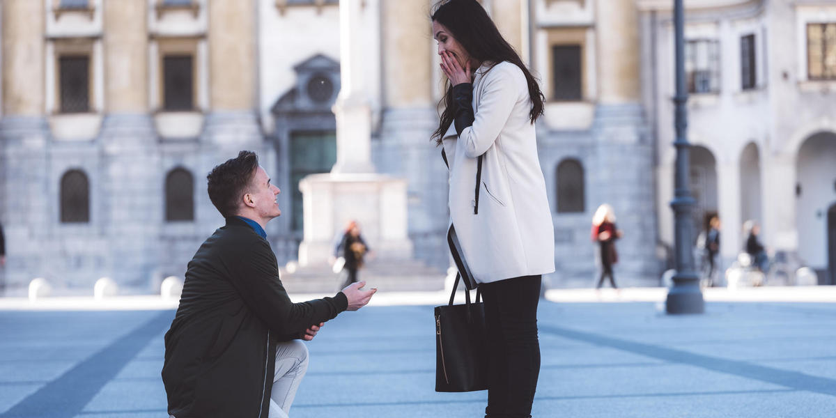 boyfriend proposing to girlfriend in middle of city square
