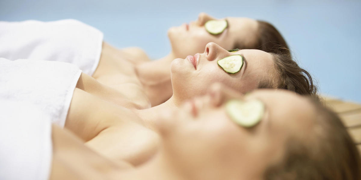 Women at a spa with cucumber slices over their eyes