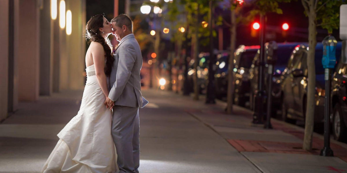 Bride and groom together on the street, holding hands and kissing